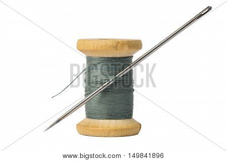 Dark thread spool and big needle isolated on white background