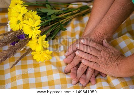 Hands of senior couple. Bouquet on checkered cloth. Best gift of fate. I'll take care of you.