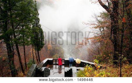 Three People Enjoying The View Of A Waterfall During Rain