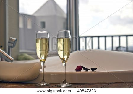 Two glasses of champagne near jacuzzi with strawberry and chocolate