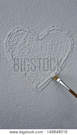 Heart on structural plaster and a paintbrush, copy space