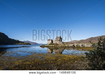 Typical Scottish scene of Eilean Donan Castle beautiful 13th century fortification at Dornie Kyle of Lochalsh in the Scottish Highlands with clear blue sky and reflections