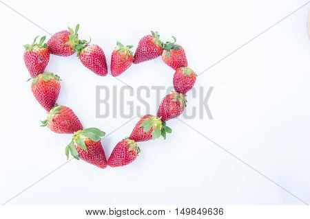 Strawberry on white background fruit's healthful cordial useful and delicious.