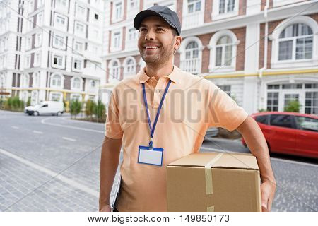 Fast and efficient service. Friendly delivery man delivering package to home, standing outdoor and smiling