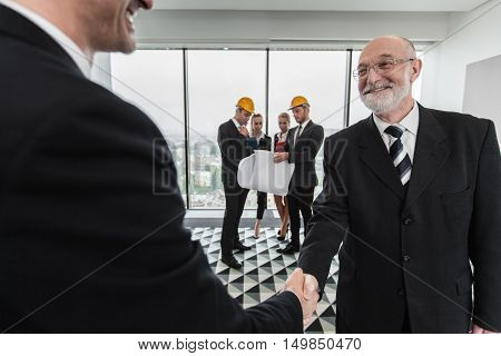 Handshake of architect and investor business team with blueprint on background