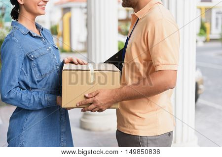 Delivery right to home. Cropped photo of delivery man giving cardboard box to young woman while standing in front of house