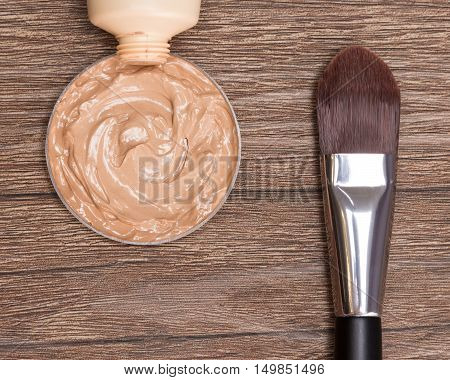 Close-up of flat makeup brush with liquid foundation squeezed out of tube on dark wooden surface
