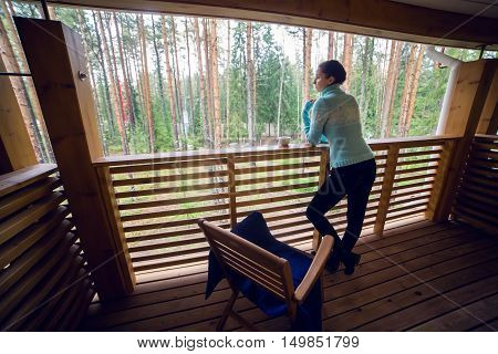 girl in a blue sweater stand and drinking teafrom a white mug on the veranda of the second floor balcony in the house in the pine forest.