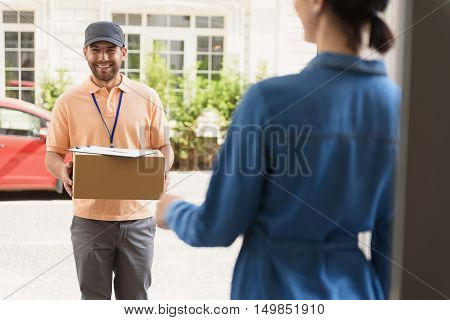 Time to get parcel. Cheerful young delivery man holding cardboard box while standing against residential house and smiling