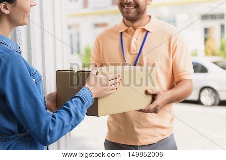 Reliable service with smile. Cropped shot of smiling delivery man giving cardboard box to young woman while standing in front of house