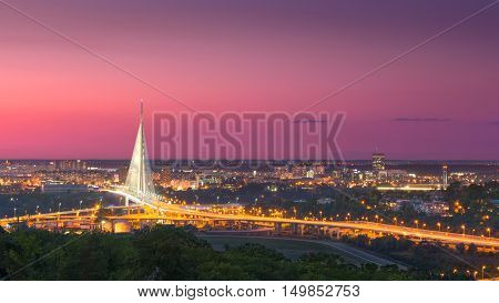 View on the New Belgrade in background Ada Bridge landmark as well as its access roads at idyllic purple sunset.