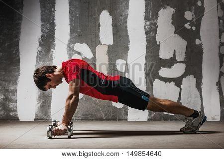 Man doing push ups on dumbbells on empty concrete backdrop