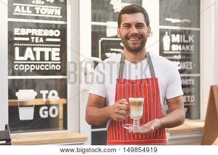 Always friendly face at cafe. Cropped shot of handsome waiter standing near cafe and holding cup of latte in his hands