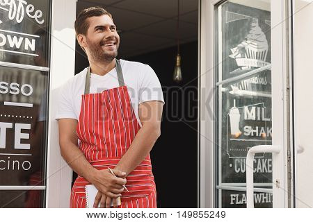 Need some great coffee. Shot of confident young waiter working while standing in doorway of coffee store