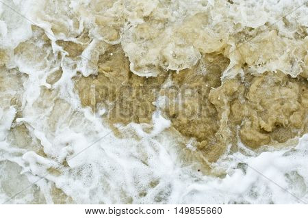 large patch of sea sand churned by rough seas and white foamy water