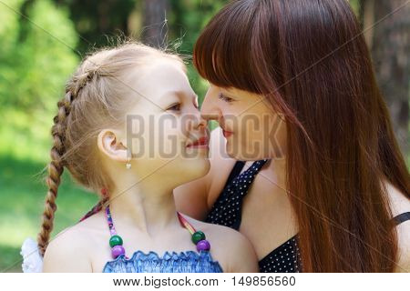 Happy mother and daughter rub noses in park at summer sunny day