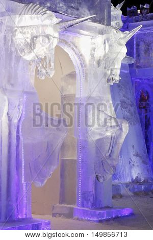 PERM RUSSIA - JAN 4 2016: Illuminated gate with unicorns in Ice town Ice town in Perm - traditional winter attraction