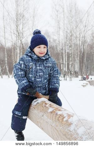Happy little boy sits on log seesaw in park during snowfall at winter day