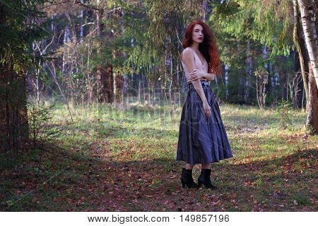 Sexy woman in skirt and belt poses on wind in autumn forest full body
