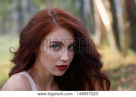 Beautiful girl with red curly hair poses in forest shallow dof close up