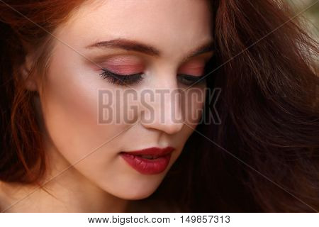 Woman with red hair smiles and looks down outdoor shallow dof close up