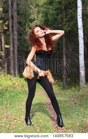 Beautiful woman in corset with fur poses in autumn forest at sunny day