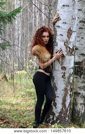Beautiful woman in corset with fur poses near birch in autumn forest