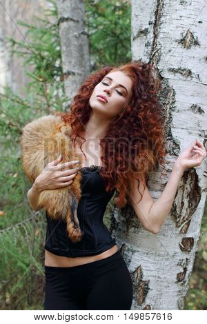 Beautiful woman in corset with fur dreams near birch in autumn forest