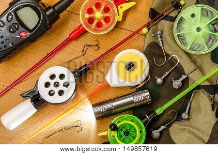 Fishing accessories consisting of tackles radio weights hook flashlight net. Wooden background. Outdoor activity and leisure concept.