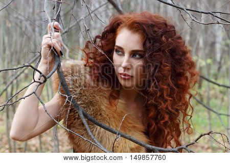 Pretty young woman keeps tree branch and looks away in autumn forest