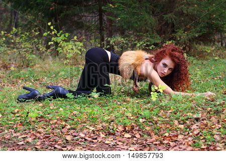 Beautiful girl with curly hair poses on grass as animal in autumn forest