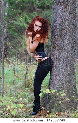 Beautiful girl with curly hair poses near big tree in autumn forest