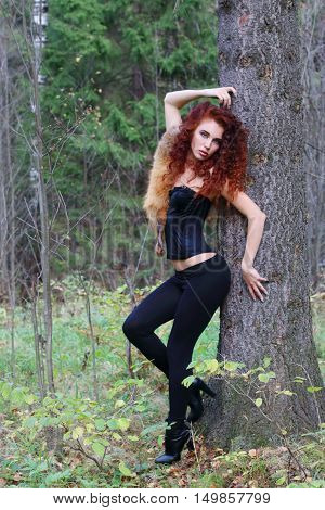 Beautiful girl in black brace poses near big tree in autumn forest