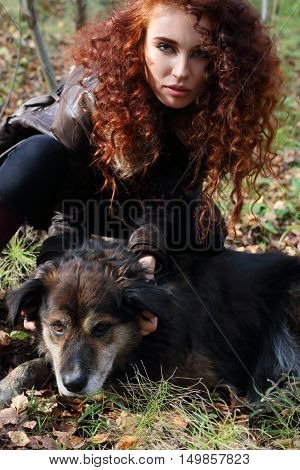 Beautiful girl in boots and jacket poses with dog in sunny autumn forest focus on dog