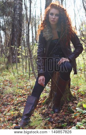 Beautiful girl in boots and jacket poses on tree stump in sunny autumn forest