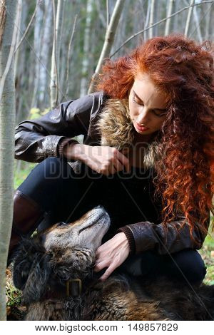 Beautiful girl in boots and jacket plays with dog in sunny autumn forest