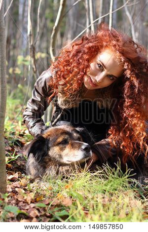 Beautiful woman in jacket poses with dog in sunshine in autumn forest