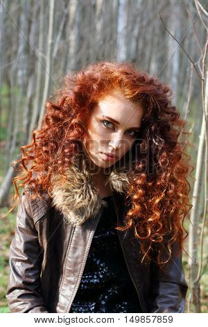 Beautiful woman with red hair in leather jacket poses in sunny autumn forest