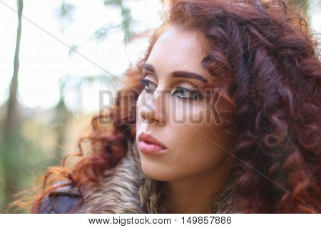 Girl with curly hair in leather jacket in sunny autumn forest shallow dof close up
