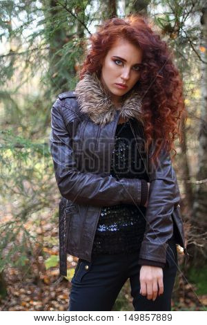Girl with curly hair in leather jacket stands in sunny autumn forest shallow dof