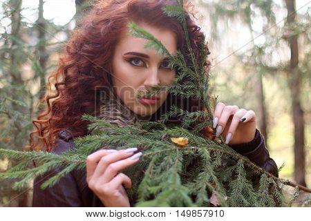 Beautiful woman looks through fir branch in forest shallow dof