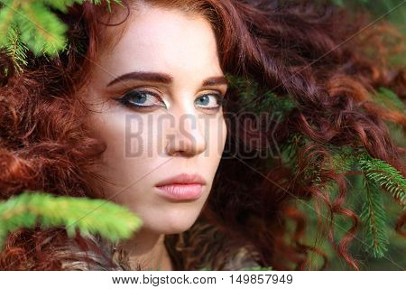 Young pretty woman poses among fir branches in forest close up