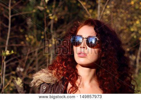 Pretty young woman in sunglasses at sunny day in autumn forest