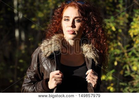 Pretty woman in jacket with sunglasses poses at sunny day in autumn forest