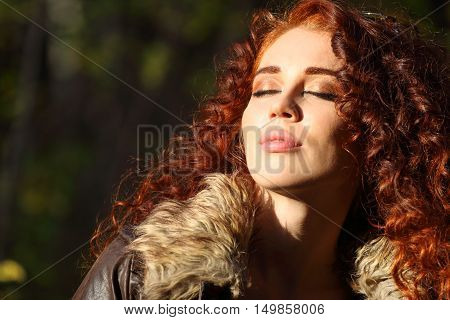 Young pretty woman with closed eyes basks in sun in forest close up
