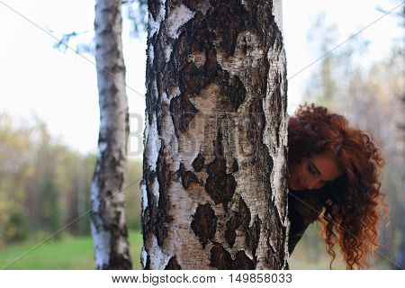 Pretty smiling woman looks out of big birch in autumn forest shallow dof
