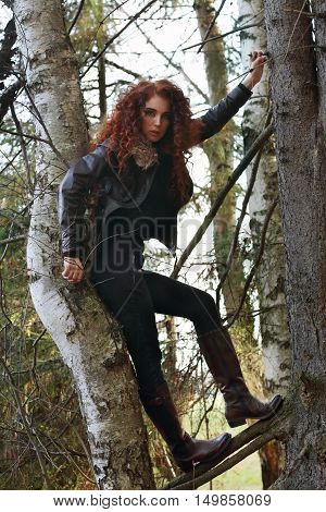 Young woman in boots with curly hair poses on old fir-tree in forest