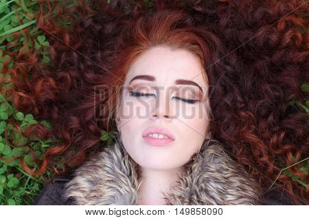 Pretty girl with red curly and closed eyes hair lies on green clover field close up