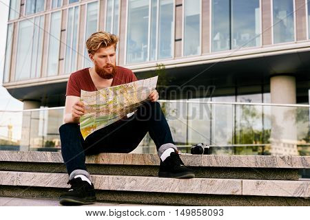Side portrait of a young strong man traveler sitting with map choose where to go. Town explorer learning the city on paper. Non technology concept.