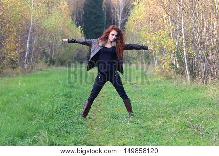 Pretty young woman in leather jacket poses on grass in autumn forest